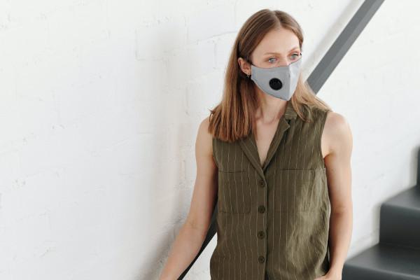 Woman wears mask in stairwell