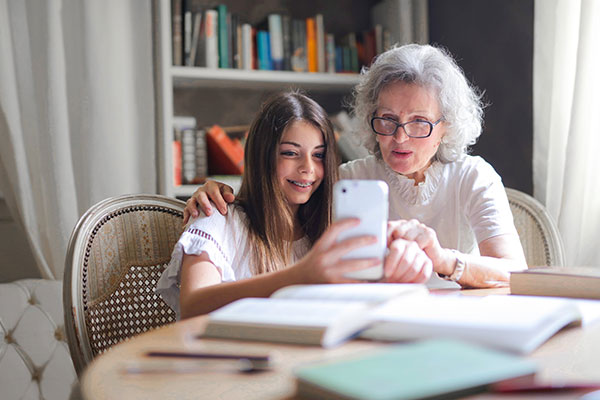 Child helping grandparent with tech